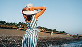 Horizontal rear view image of brunette beautiful woman with white hat, walking along the beach at seaside on the sunset background. Female wearing striped dress posing outside during vacation. Travel concept.