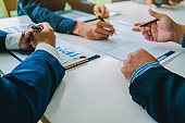 Customers sign a contract on paper letter from salesman in the office for make a purchase agreement.