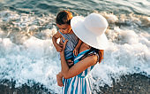 Horizontal top view image of pretty young mother playing with her daughter at the seaside, wearing blue striped dress and white hat background. Female playing with cheerful little girl at ocean sunset