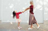 Side view image of beautiful mother looks to her little girl holds the hands together and dancing outside near their home. Daughter playing with her mom feeling happy. Woman and child shares love.