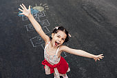 Above view image of happy little girl playing hopscotch on playground outdoors. Child feels happy during playing the game outside. Kid plays hopscotch drawn on pavement. Activities, games for children
