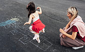 Rear view image of little girl playing hopscotch with her mother on playground outdoors. Child plays with her mom outside. Kid and woman plays hopscotch drawn on pavement. Activities and games outside