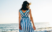 Horizontal rear view image of brunette beautiful young woman walking along beach and sea at the sunset sunlight background. Pretty female wearing dress, walking outside on the ocean.