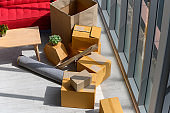 Cardboard boxes stacked, plants, comfortable couch near big window inside of modern living room in new house, celebrating moving to new home concept, no people. top view
