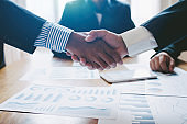 Young man business people shaking hands after brief job for contract signing in modern office with vintage picture style, colleagues at meeting teamwork of partnership.