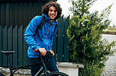 Young man walking with his bike after bicycling down the street on a rainy day next to the fence's house. Smiling male courier with curly hair delivers parcel cycling with a bicycle.