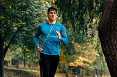 Horizontal image of young jogger man jogging outdoor in the nature background. Fitness male exercising in the park, wearing blue and black sportswear. People and sport concept