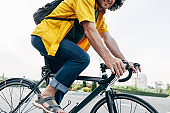 Closeup cropped image of a young man in yellow shirt cycling on his bike in the city street. Male courier with curly hair with backpack delivers parcel cycling with a bicycle in the city.