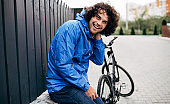 Cheerful Caucasian man with curly hair sitting on the fence with his bike before bicycling next to the house. Happy male courier with curly hair delivers parcel with a bicycle in the city.