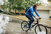 Horizontal outdoor image of handsome man cycling on his bike down the street next to the house. Caucasian male courier with curly hair delivers parcel cycling with a bicycle in the city in a rainy day