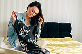 Indoor image of young woman smiling broadly sitting on the bed and unpacking the parcel with new dress. Happy female receive a gift for her birthday at home. Online internet commerce delivery concept