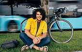 Horizontal image of happy young man relaxing after cycling on his bike in the city street. Male student with curly hair in yellow shirt sitting outdoor on the green grass after cycling with a bicycle.