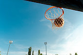 Outdoors basketball, ball coming through the hoop , no people in the shot