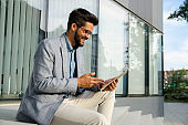 Elegant young businessman in suit sitting in front of modern office building and using tablet