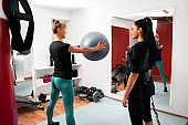 Trainer woman teaching trainee in ems suit, with Pilates ball