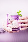 Beautiful female hands holding glass with macaroons on the pale violet pink background
