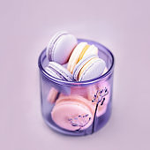 Pale purple glass with macaroons or macarons on the gray background. Glassware made of recycled glass