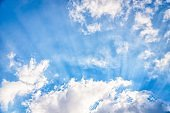 Amazing blue sky with fluffy clouds and sun rays. Beam of light, sky background
