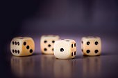 Four dices on a dark purple violet background, copy space