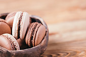 Homemade delicious chocolate and vanilla macaroons in a ceramic bowl on a wooden background. Copy space.