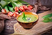 Homemade green spring cream soup with wild leek on a wooden background. Red orange tulips flowers