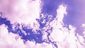 Sky background. Beautiful pink purple sky with white clouds. 16:9.