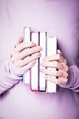Beautiful female hands holding four books on the pale violet background. Manicure with pink color nail polish with shiny design, nude manicure, copy space