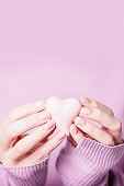 Beautiful female hands holding pink heart