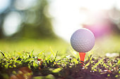 golf ball on tee in a beautiful golf course with morning sunshine.
