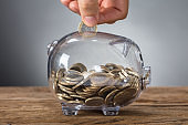 Hand Inserting Coin In Transparent Piggy Bank