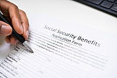 Person's Hand Filling Social Security Benefits Application Form