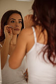 Mid adult woman checking for wrinkles and imperfections in the mirror