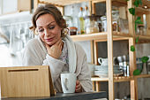 Smiling mature woman enjoying her morning coffee and talking with a friend over a video call