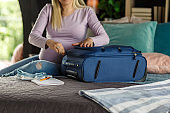 Pregnant woman packing a traveling bag for delivery day