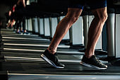 Unrecognizable male athlete training his endurance by running on a treadmill