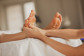 Close up of a massage therapist massaging client's feet at the spa