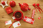 Flat lay of Valentine's day themed chocolates and love notes with tea and a gift