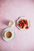 Copy space of delicious waffles and coffee on a pink background