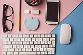 Essential office tools on pink and blue background