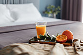 Breakfast tray with orange juice on a bed in a hotel room