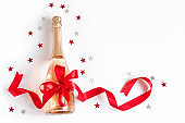 Champagne bottle with red ribbon and stars