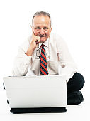 Smiling, confident businessman sits on floor with open laptop