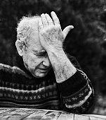 Senior man clutches his forehead in grief or despair