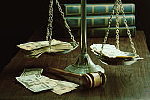 Cash on the scales of justice symbolizes bribery or the high cost of legal action