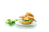 Homemade bun with cheese spread, fresh arugula and boiled egg in a plate