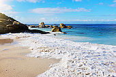 Waves roll in from a beautiful ocean on to an idyllic sunny beach with rocks in the distance