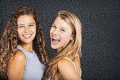 Lovely young woman and teenage girl share a moment of joy, faces close to each other