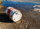 Old oil drum lies next to a stream, posing threat of pollution