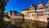 Idyllic panorama in a German old town on a river with city wall and half-timbered houses