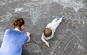 Young boy doodling on asphalt with his mother